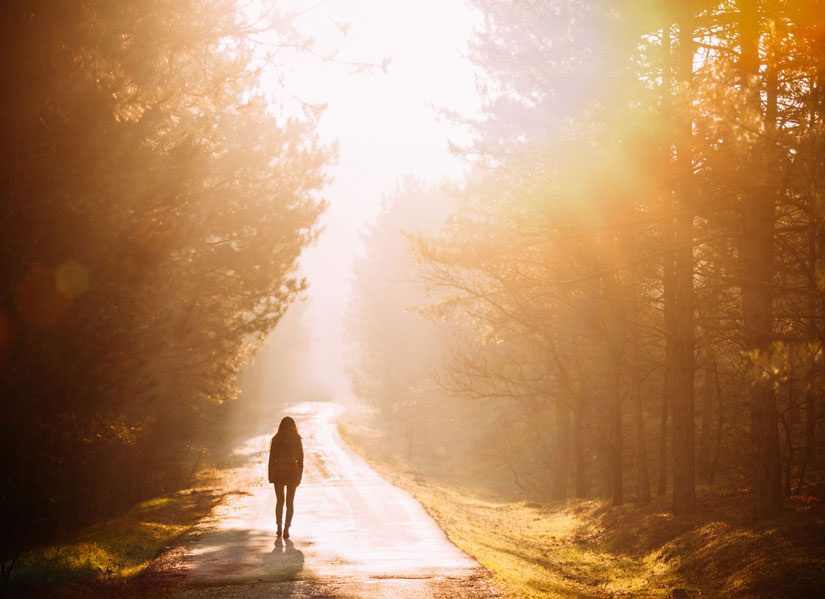 Person walking on sunlit path